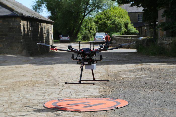 Гексакоптер DJI Matrice 600 Pro взлетает с полезной нагрузкой для выполнения LiDAR-сканирования и создания 3D-картографии.