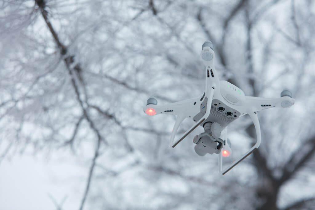 Квадрокоптер DJI Phantom 4 на фоне зимнего леса