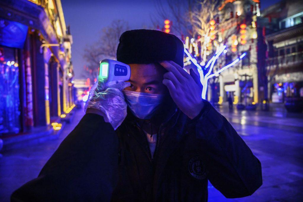 Проверка температуры человека с помощью инфракрасного термометра на улице